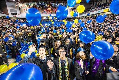 University of Alaska Fairbanks graduates reach for balloons at the end of UAF's 97th commencement ceremony, held May 4, 2019, at the Carlson Center.