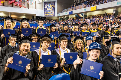 University of Alaska Fairbanks graduates from the College of Engineering and Mines and the College of Natural Science and Mathematics display their diploma covers during the commencement ceremony at the Carlson Center on May 4, 2019.