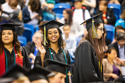 University of Alaska Fairbanks School of Management graduate Briona Hudson waves to the audience during UAF's 97th commencement ceremony at the Carlson Center on May 4, 2019. Hudson received a bachelor's degree in business administration.