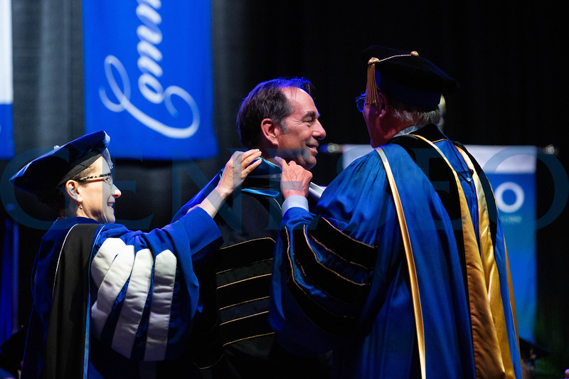 President Denise A. Battles and Robert (Bob) Wayland-Smith hood Joseph Carr, this year's honorary degree recipient