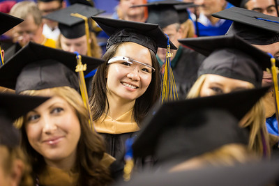 Sporting a pair of Google Glass, M.B.A., in Business Administration student, Venus J. Sung, sits next to her fellow classmates at the School of Management section during the 2014 UAF Commencement Ceremony.  Filename: GRA-14-4187-239.jpg