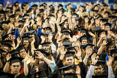 Graduates raise their hands after a prompt by Class Speaker Ashley Strauch's interactive address during the 2014 UAF Commencement Ceremony at the Carlson Center.  Filename: GRA-14-4187-279.jpg