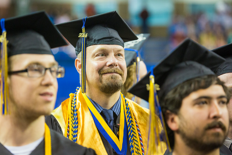 "Troy Bouffard is all smiles after returning to his seat during the 2014 Commencement Ceremony Sunday, May 11, 2014 at the Carlson Center. Bouffard received a B.A., in Political Science, cum laude.  <div class=""ss-paypal-button"">Filename: GRA-14-4187-179.jpg</div><div class=""ss-paypal-button-end""></div>"