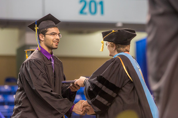 """Milaud Baumgartner accepts his degree in mechanical engineering during UAF's commencement ceremony May 11 in the Carlson Center.  <div class=""""ss-paypal-button"""">Filename: GRA-14-4186-0368.jpg</div><div class=""""ss-paypal-button-end"""" style=""""""""></div>"""