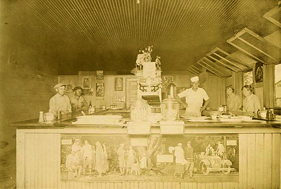 Café located on S. Jefferson Street, circa 1930, operated by Omer Bennett. Omer Bennett is the chef standing behind the counter. Sitting to his left are Annie Ruth Taylor Griffin (Mrs. Foster Griffin) and Vera Bennett. Johnny McDowell's cafe was later at same location.(Courtesy of Zona McGuirt, niece of Omer Bennett)