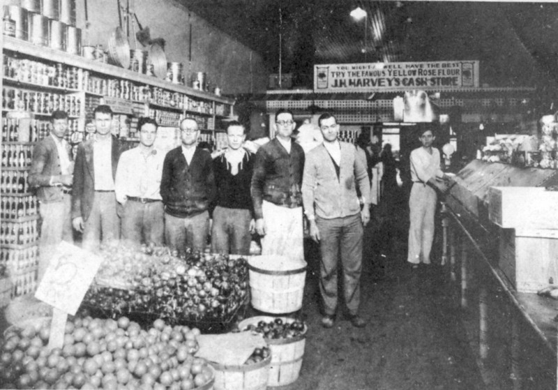 "J. H. Harvey Cash Store, circa early 1930's<br /> Cutline from Berrien Press, date unknown:<br /> Down Memory Lane with Berrien Press<br /> Merchandising was quite different back in the early 1930's when the J. H. Harvey Cash Store was on the corner of S. Davis St. and W. Washington Ave. Customers would come in with their list of groceries and the clerks would give individualized, personalized service to each one. Behind the sign ""5¢ Dozen"" for oranges are clerks, left to right: Ernest Bennett, H. E. Whaley, unidentified, J. Howell Giddens, June Avera, W. E. Lester and R. C. Lester. Harvey's moved to the E. Marion Ave. location about 1934, to the present location in April 1964 and expanded a few months ago."