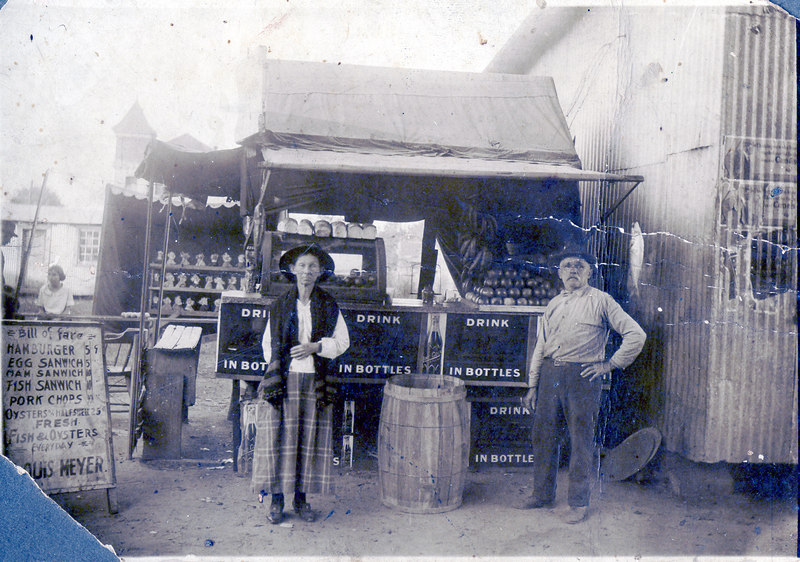 Serena Thompson Meyer and Louis Frederick Meyer grocery stand on Jefferson Street behind where the old post office Service Station was located (Bailey Appliance building). Al and Pauline VanMeter in the background (Pauline was a daughter of Serena and Louis). Note jail in far back ground. This fertlizer warehouse on right was torn down in 1959