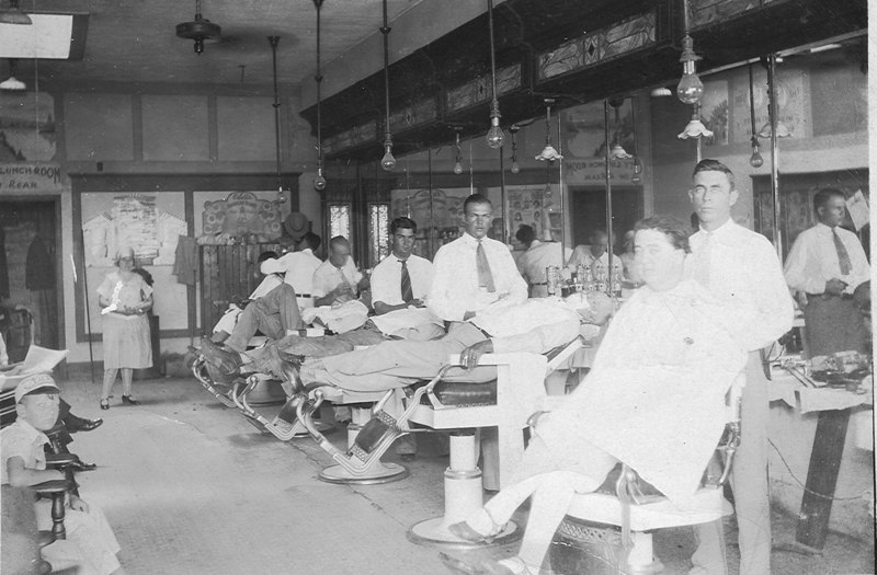 """Barber Shop in the Marion Hotel. Note the sign over the doorway in the background reads """"City Lunch Room in Rear""""<br /> R-L: Clarence Akins, Esetelle Lee Akins, Blake May, Battie Gaskins, Terry Shaw, Glen May, Ava Nell Gaskins May (Mrs. Ethridge Lee Sirmans in background), circa 1930s. (Courtesy: Kenneth May, Sr.)"""