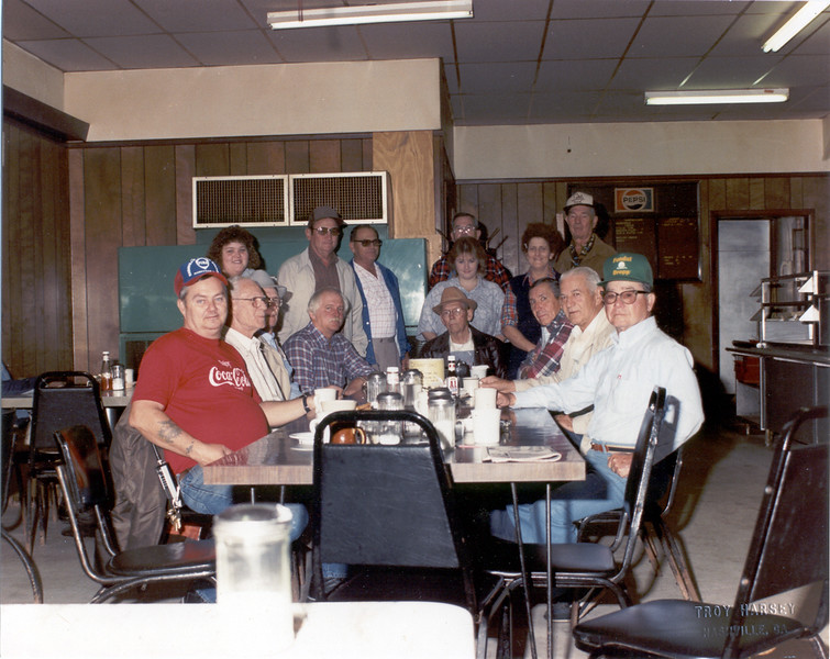 'Men's Gossip Table' at the Dinner Bell on northside of the square in 1990. Wendell Richwine, Acie Griffin, Sly Faulkner, Lamar Gray, Robert Hancock, William Henry (Buddy) Rowe,---, Amos Lindsey, A.J. Powell, ----, Andy Croft, standing far back: Rob Jackson, Dinner Bell Owner Jane Cersey and Daughters.