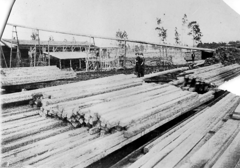 Berrien Lumber Company, also known as Ruby Sawmill, operated by Drew Fuller from about 1918 to 1925. It was located in the community of Ruby three miles west of Nashville off the Adel Highway. It was one of the most modern sawmills of the time. Shown are stacks of boards and the pipe that carried bark removed from timber.