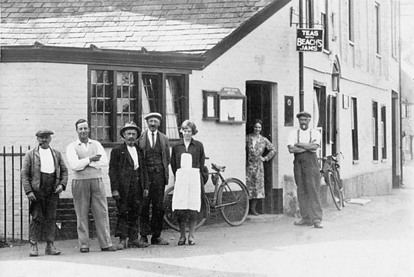 <font size=3><u> - The Crown - Pre 1935 - </u></font> (BS0192)  Also used as a tearoom. Bert Passey is seen in a cap, next to one of his sisters.  George Arlot wears the pullover.   Mrs Arlot is in the doorway.  Mr Wigmore – gardener for the Crown – is on the left of picture.