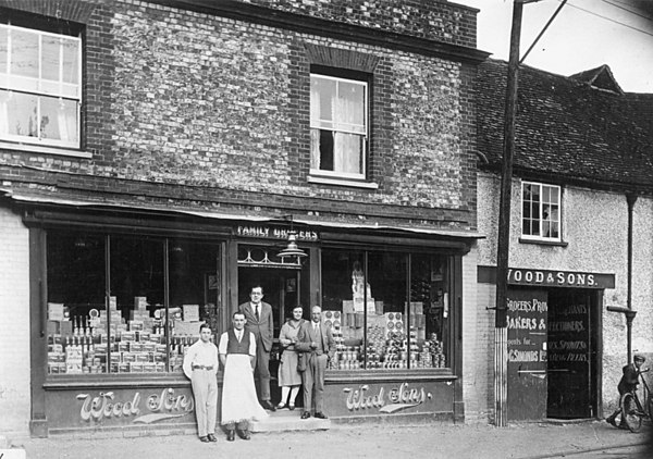 <center><font size=3><u> - Woods the Grocer's in Castle Square- </u></font> (BS0351)  Of the 5 people in the shop door, as you look at the picture, old Mr Wood, and behind him his friend from Chalgrove Alice Fidget.  Young Mr John Wood stands in the doorway.  Man with apron is Sammy Lawrence, who apparently sang so loud off-key that the Vicar invited him not to come to Church!  The boy on the left is thought to be Tommy Selwood.   Boy on extreme right with bike is one of the Harbor boys who lived in a house opposite.  </center>