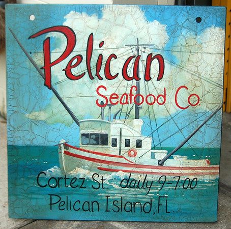 'Pelican Seafood Co' outdoor sign with shrimp boat