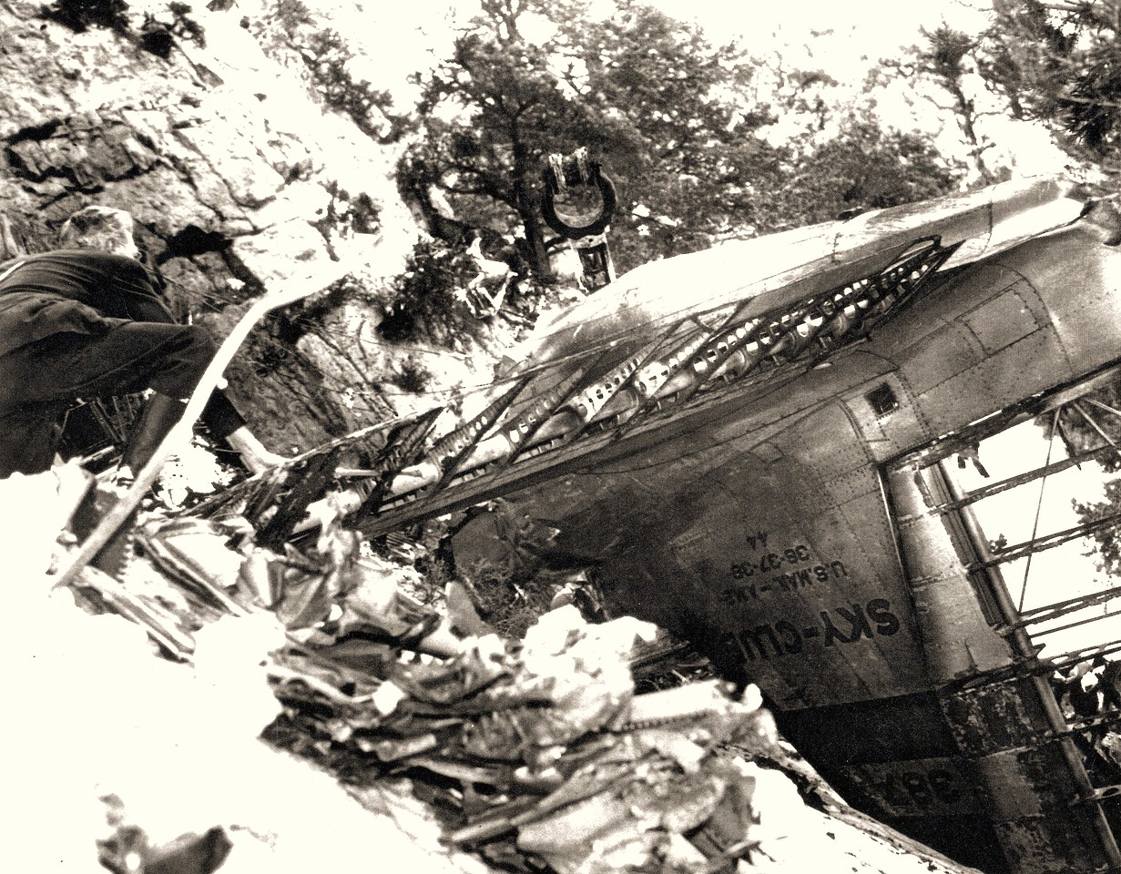 A CAB accident investigator examines the inverted tail section of NC1946. One of the few pieces of aircraft structure that survived the impact and post impact fire. (Bettman Archives)