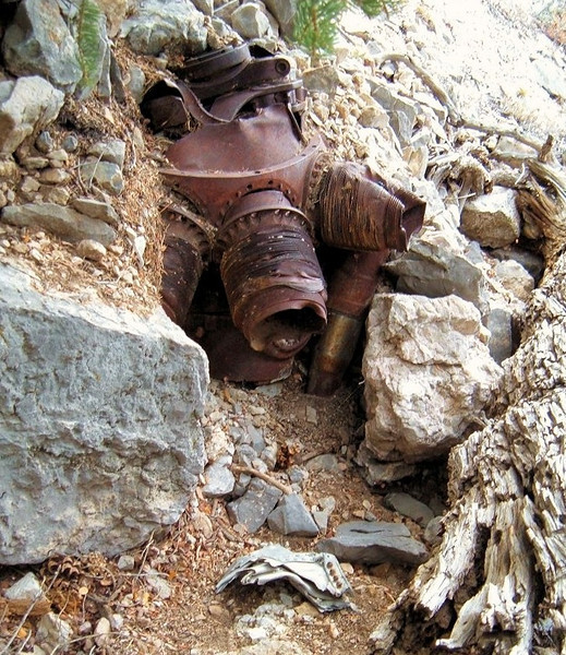 The port side (#1) engine was was found in a gully below the main impact site and below the #2 engine. <br /> <br /> It was partially buried by washed down debris and had visible impact damage from the cliff face. (Lostflights Photo)