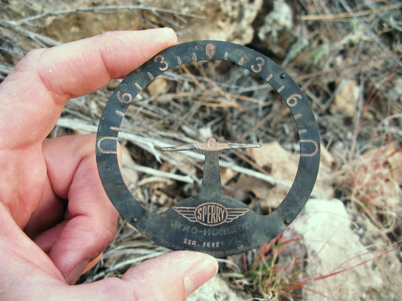 This faceplate from the Sperry Auxiliary Gyro Horizon instrument was located during the early 1990s with other cockpit wreckage debris. (Lostflights Photo)
