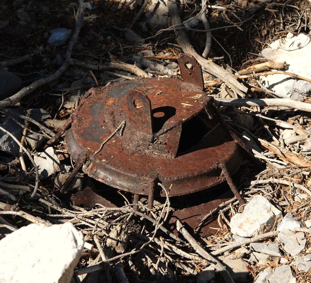 EVIDENCE OF SALVAGE<br /> <br /> This mystery object located at the crash site was not part of the aircraft. <br /> <br /> It appears to be the mounting base for a makeshift smelter used by salvage workers attempting to recover the aluminum wreckage for profit. (Lostflights Photo)