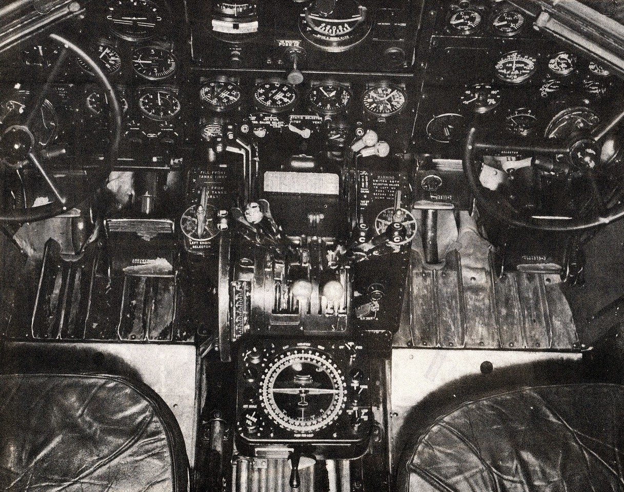 The flight compartment on an early 1940's era TWA Douglas DC-3. Center pedestal with throttle, propeller and fuel mixture levers. <br /> <br /> Between the two pilot's seats is the Sperry Automatic Direction Finder which played a significant roll into the disaster and will be discussed later. (TWA Photo)