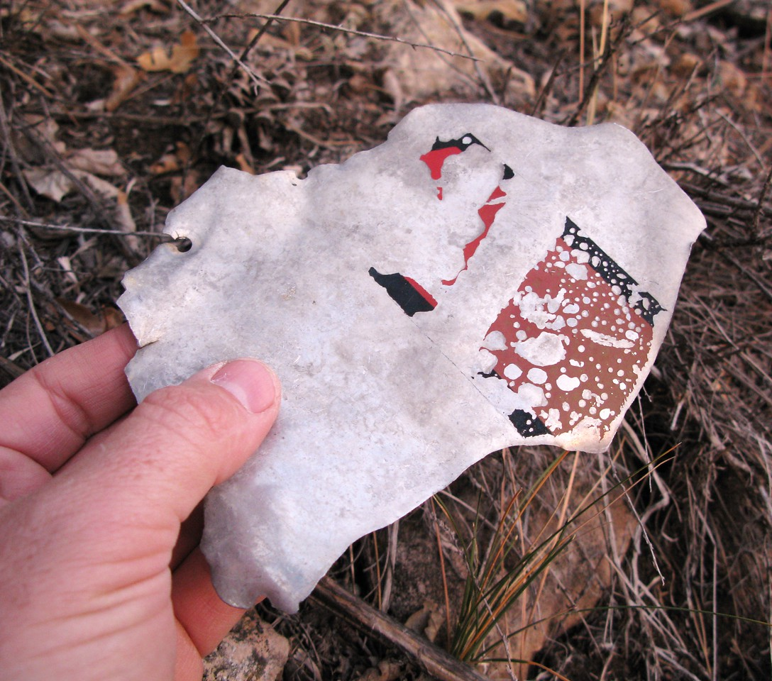 "This fragment, based on the size and style of the painted red/black lettering was most likely from the DC-3's tail (vertical stabilizer). Probably from the name ""SKY CLUB"" or the TWA line number ""387"". (Lostflights Photo)"