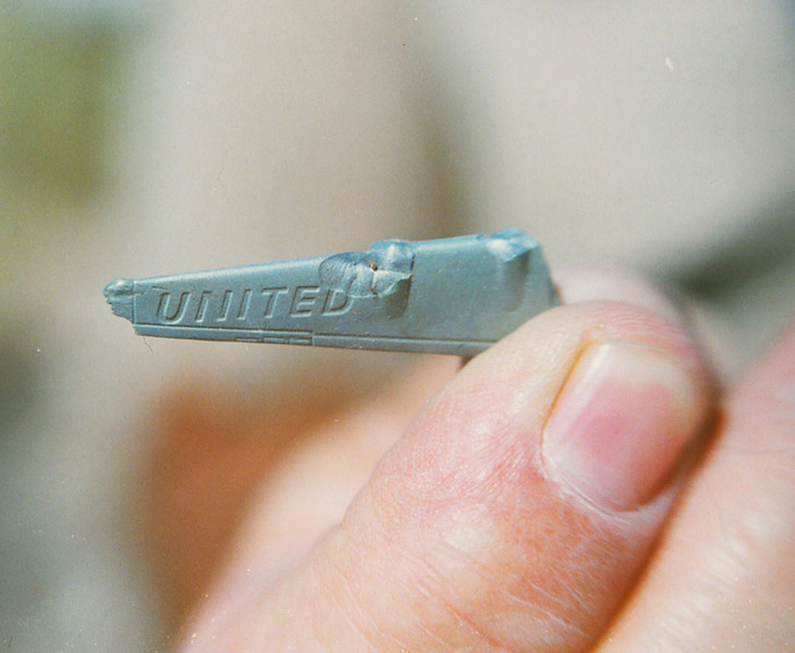 The remains of a small plastic wing from a toy DC-7 airplane.<br /> <br /> These toy airplanes were given to child passengers by the airline stewardesses and pilots.