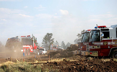 Multi-Agency Firefighting personnel work to contain the brush fire on the mesa.