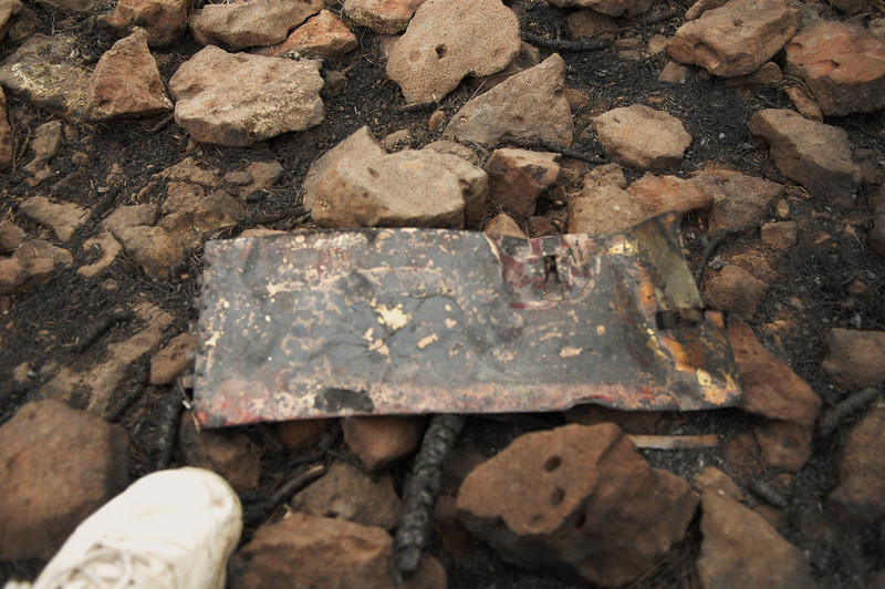 An engine access panel door (left side) with two Hartwell Latches was found burned about 100 feet southeast of the Guardian Air impact site. <br /> <br /> The small traces of red paint still visible indicate the panel was from the Guardian ship (Classic would have had blue paint on this particular panel). (2008 LostFlights)