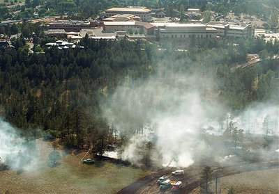 Flagstaff firefighters work to put out a blaze shortly after two medical helicopters collided Sunday, June 29, 2008, about a half-mile from east of Flagstaff Medical Center. The Flagstaff Medical Center is seen in the background. (AP Photo/Flagstaff Police Department)