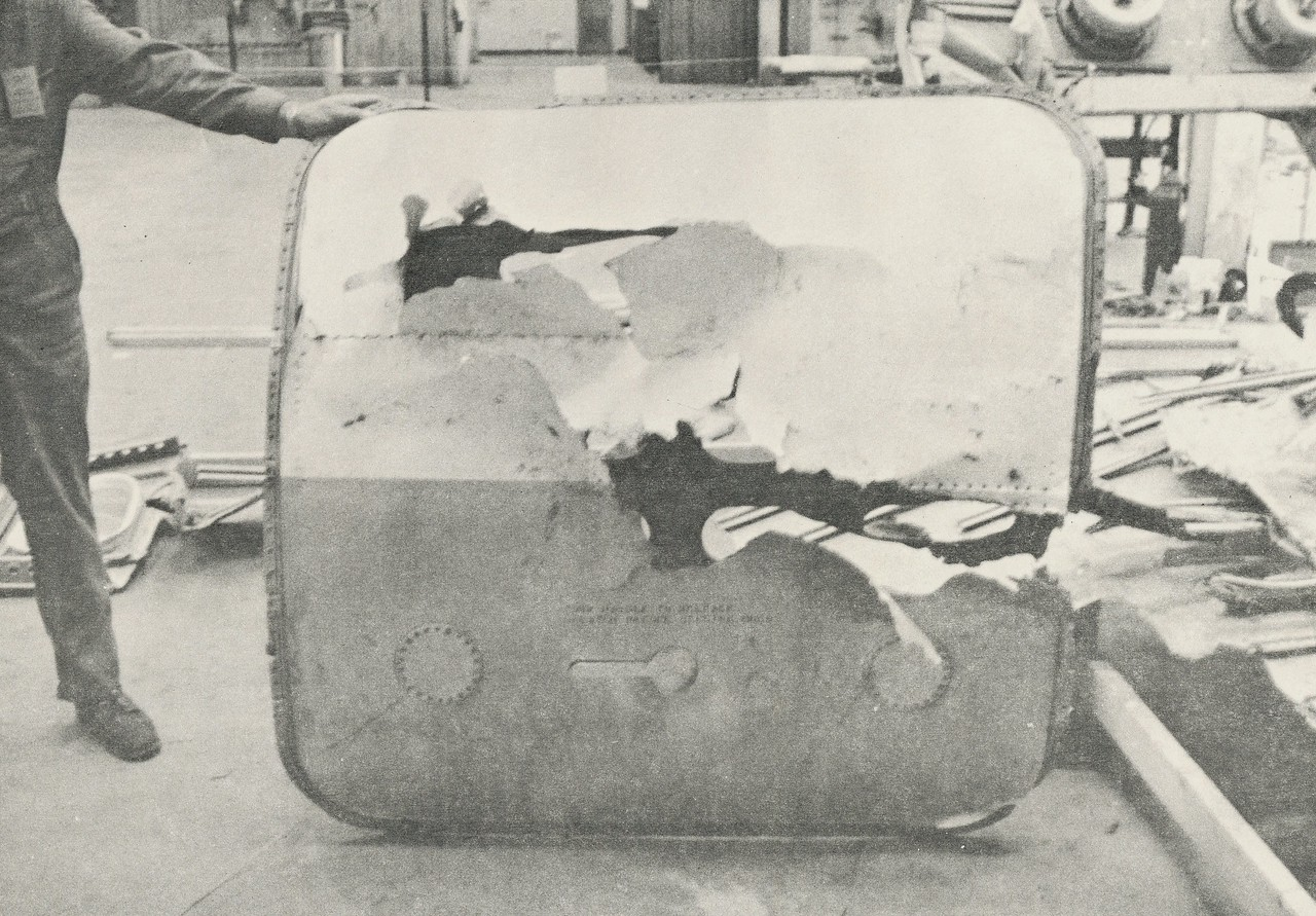 "A ""key"" piece to the accident investigation was the recovery of the DC-9's forward baggage door. Located on the right side of the DC-9's fuselage and opposite of the initial impact point. The photo illustrates how the forward baggage compartment was breached while damage is visible on the exterior and interior sides of the baggage door. (LostFlights File Photo)"