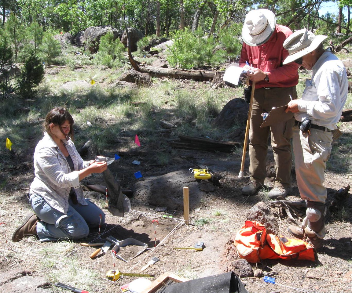 USFS Archaeologist Cristin Embree recovering a buried piece of wreckage as Matt Wheling and Bob Rushforth record the find.