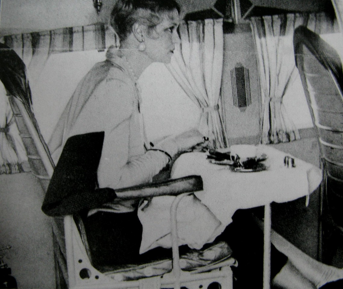 A vintage TAT airline promotional photo showing a passenger seated for meal service in the Ford Tri-Motor.