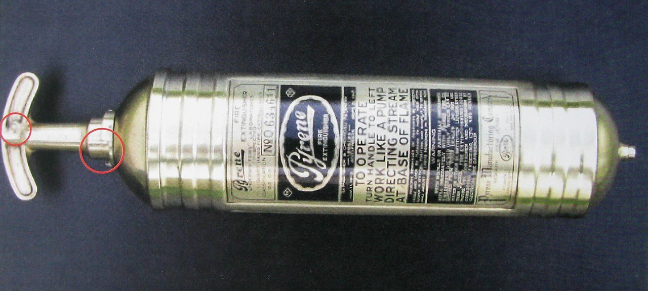 An example of an undamaged Pyrene fire extinguisher. The components circled match the recovered artifact above.<br /> <br /> These fire extinguishers were generally mounted to the interior walls of the Tri-Motor's passenger cabin.
