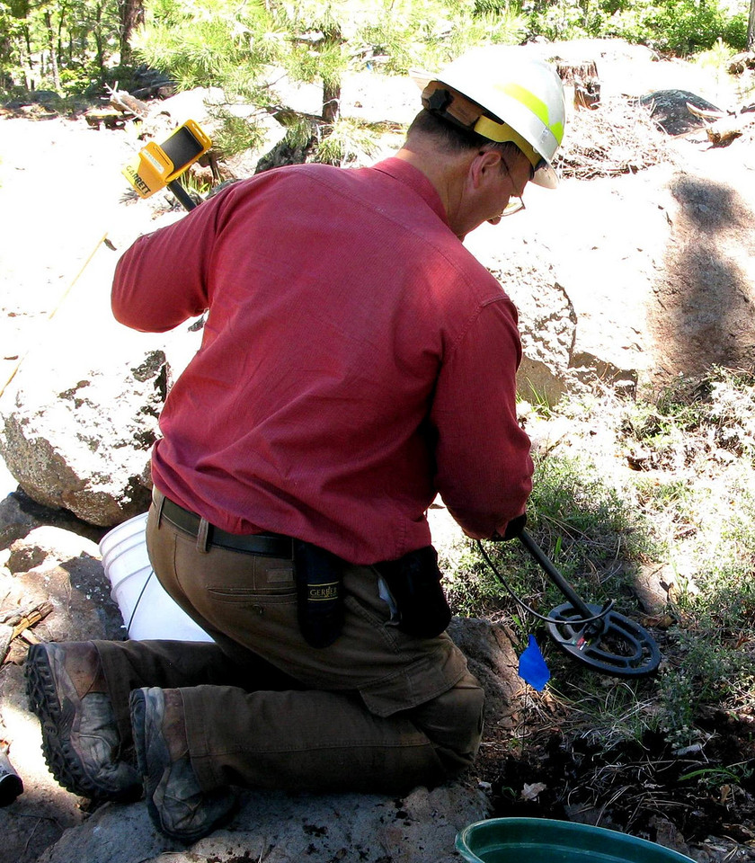 Matt Wehling conducts a final search for surface metal objects with a metal detector prior to setting up an excavation grid at the main impact site.