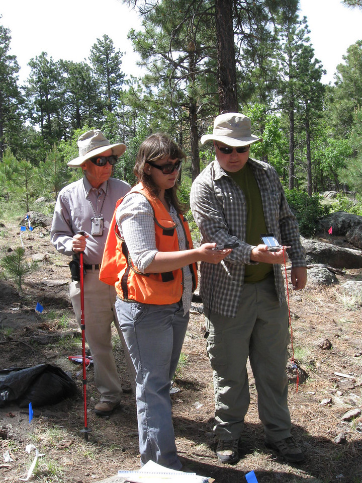 Cristin Embree and Craig Fuller compare compass readings during the survey and mapping process.