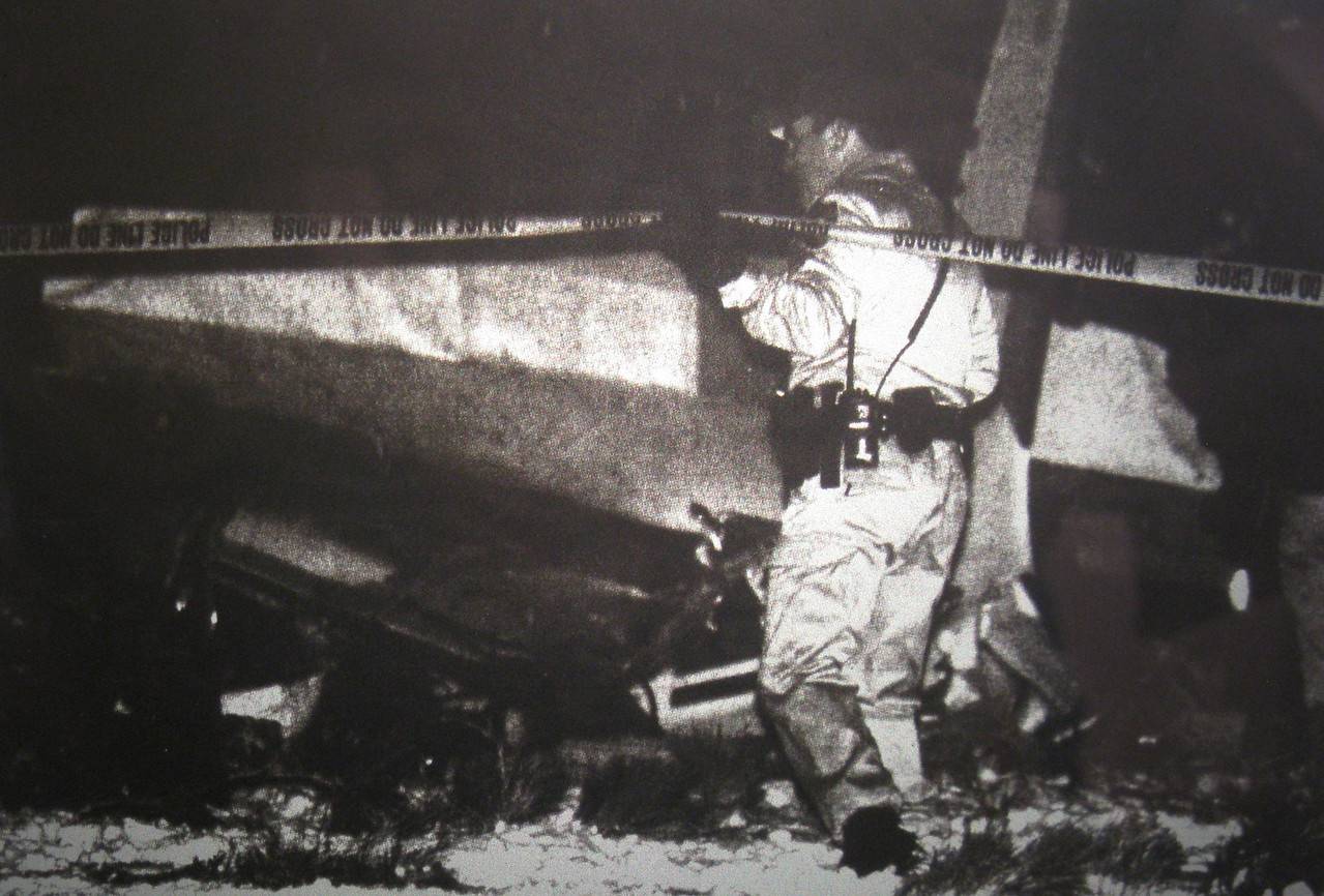 """An Arizona Department of Public Safety officer examines the wreckage of """"N592DM"""". The accident occurred at night during inclement winter weather conditions."""
