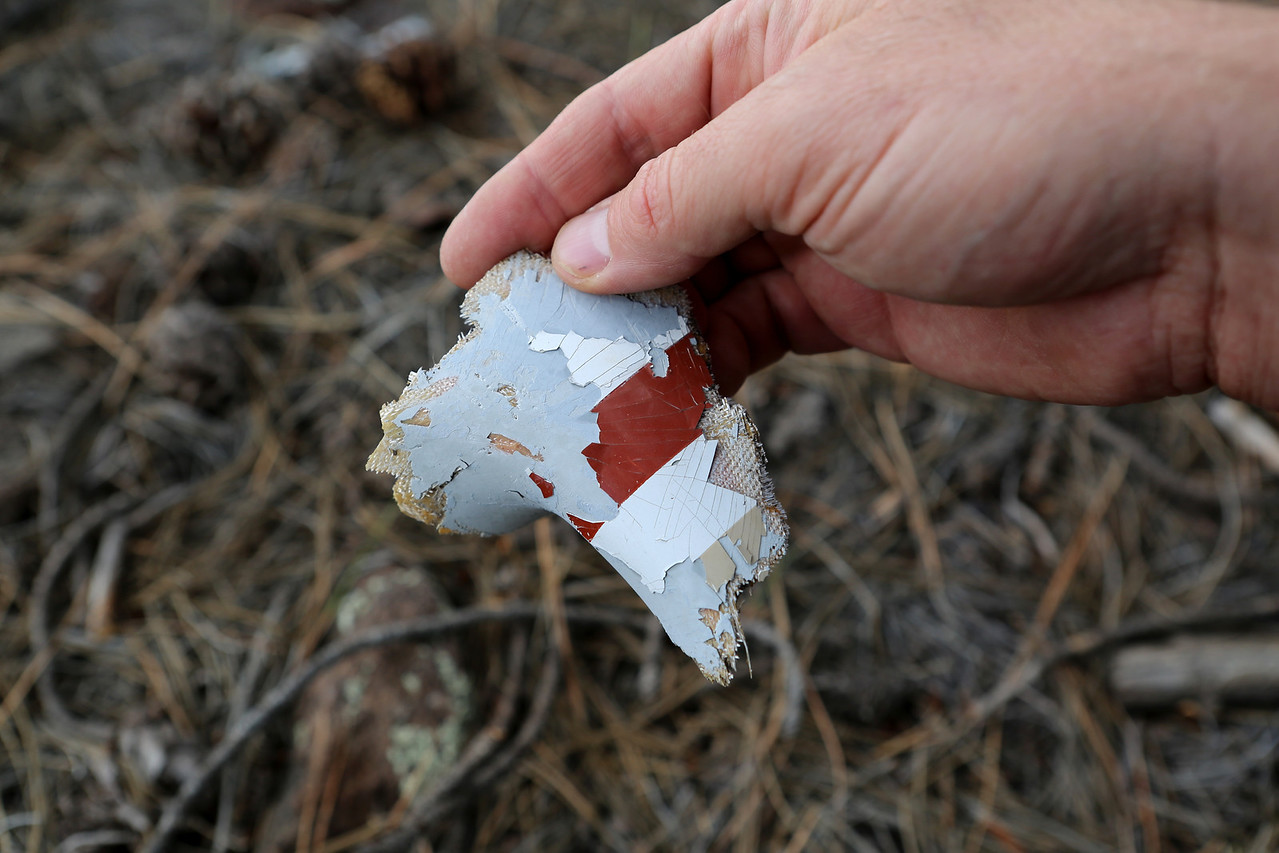 A painted fiberglass fragment was found at the site displaying part of the aircraft's white/brown paint scheme.