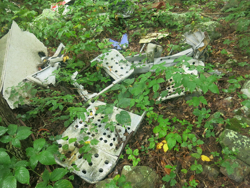 A small pile of passenger seatbacks and seatpans. Although many were found, it was apparent many more were missing from the crash site (the aircraft had a seating capacity of up to 44 passengers). <br /> <br /> The missing seats were possibly recovered by accident investigators to study the structural integrity of the seats in the accident.