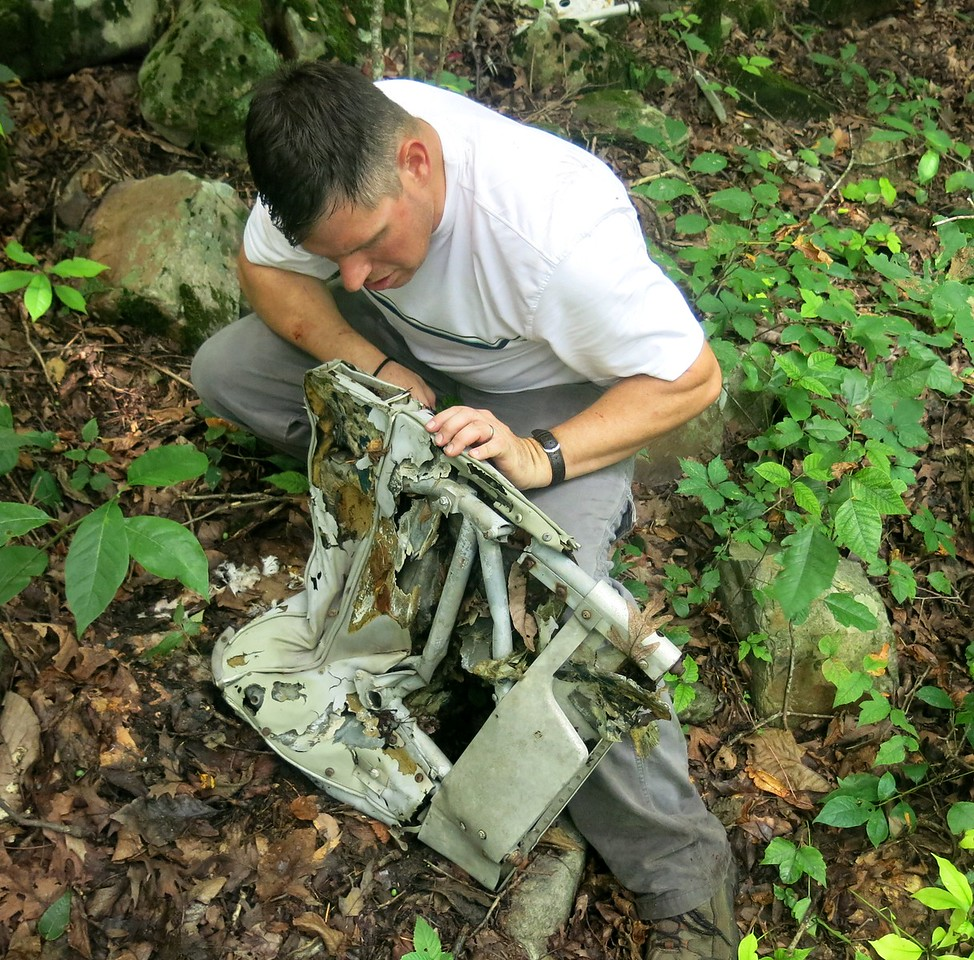 Jeff Wilkinson examines the seatback of what is believed to be a pilot crew seat.