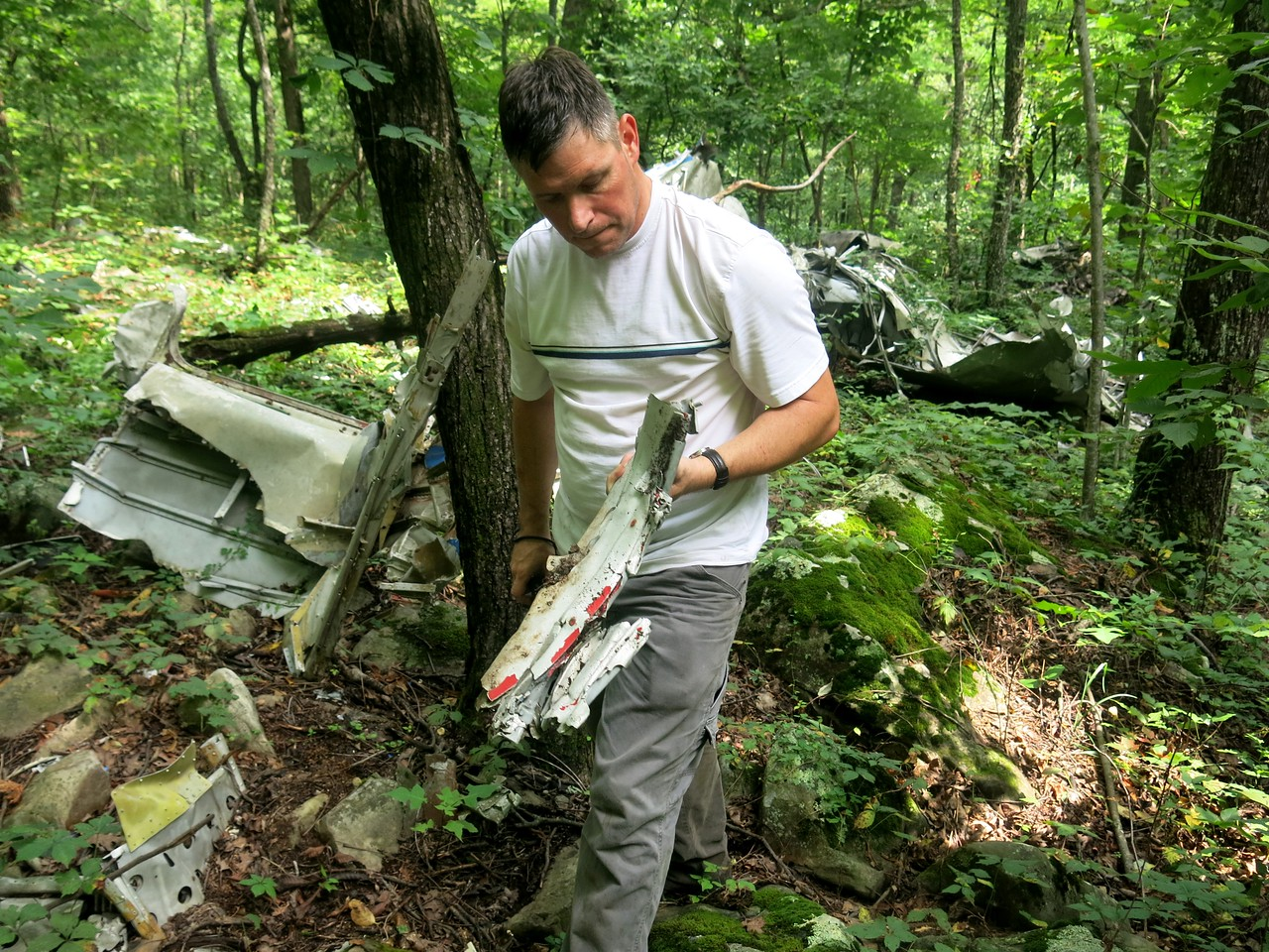 """Jeff holds up a crushed fragment of aircraft structure. Many fragments at the site exhibited """"accordian"""" type impact bends from striking numerous trees during the structural break-up of the aircraft."""