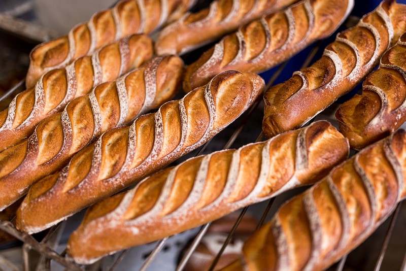 decorated bread loaves and baguettes on shovel coming out of the over in bakery shop. bread bakery concept with warm
