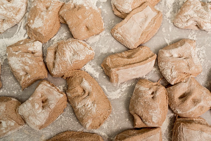 close up of uncooked bread shapes of fresh dough with flour on shelf before entering the oven for baking. flat lay of fresh round bread in bakery factory