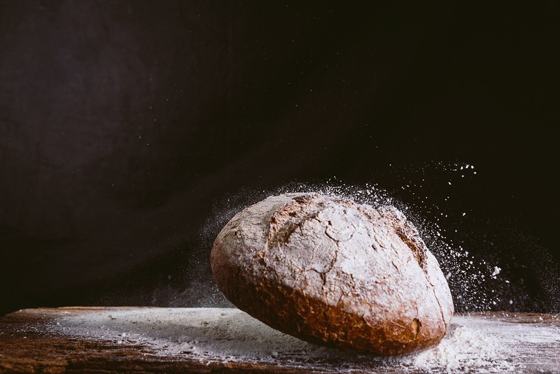 spectacular image of fresh and rustic golden bread falling on wood kitchen table with flour explosion against black background. concept of bakery and healthy eating