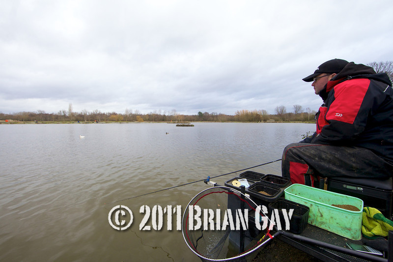 waiting for a bite, Will Raison fishes a small cage feeder with dead maggots and fishmeal for bream. © 2012 Brian Gay