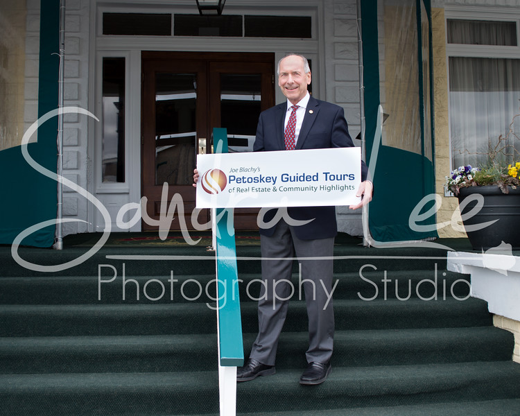 Realtor Joe Blachy holds a sign advertising his new guided tours of Petoskey real estate and community offerings.<br /> <br /> Real Estate Photography <br /> Need a portfolio of your property?<br /> Call Sandra Lee today...<br /> <br /> Sandra Lee Photography Studio & Gallery<br /> Petoskey, MI<br /> 231-622-2066