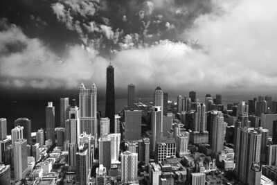 A black and white aerial photo of downtown Chicago facing east over the Chicago River. In this photo, the John Hancock, Water Tower Place and Lake Michigan.