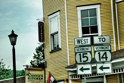 Road signs in Hardwick, Vermont near Connie's Kitchen Bakery & Deli.
