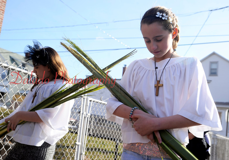 Alyssa Snyder, left, and Emma Tomcavage pray while the St. John's United Methodist Church parish hall in Coal Township is blessed during Palm Sunday worship.