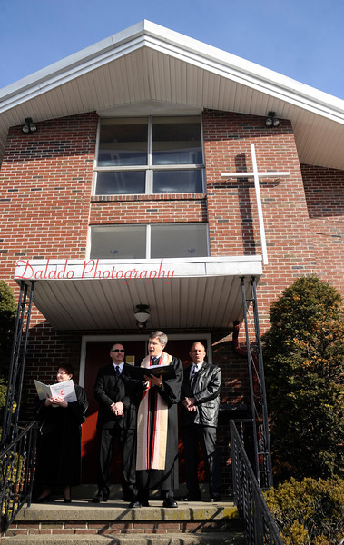 Rev. Gary Nicholson, northwest district superintendent, blesses the St. John's United Methodist Church parish hall in Coal Township is blessed during Palm Sunday worship. The congregation moved to the parish hall, which was built in 1963. Also pictured are Rev. Karyn Fisher, pastor; Steve Van Doren and Scott Appel.