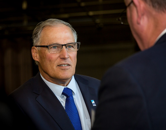 Governor Jay Inslee speaks to constituent at corporate event.