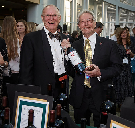 Well dressed gentlemen checking out wine at the FareStart auction table.