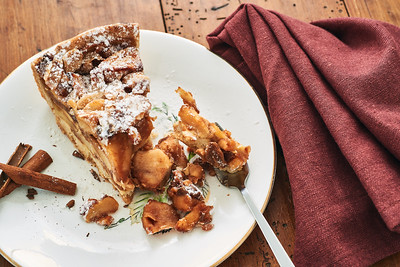 A piece of homemade apple pie and a chunk on a fork